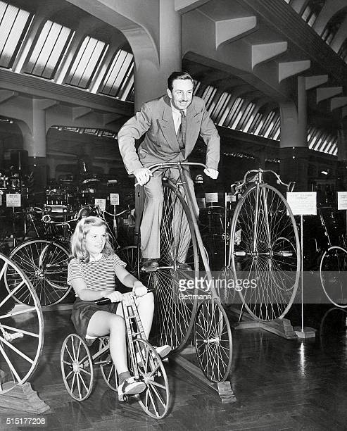 Walt Disney takes an imaginary spin high on an old Eagle racing bike while his daughter Diane paces him on an 1870 model tricycle The bikes are part...