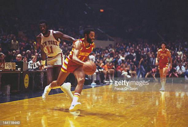 Walt Frazier of the Cleveland Cavaliers dribbles the ball up court away from Bob McAdoo of the New York Knicks during an NBA basketball game circa...