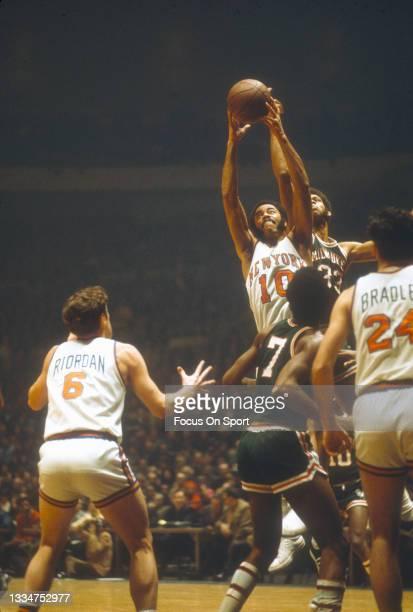 Walt Frazier of the New York Knicks grabs a rebound away from Kareem Abdul-Jabbar of the Milwaukee Bucks during an NBA basketball game circa 1975 at...