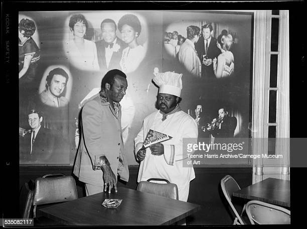 Walt Harper and Bob McCall wearing chef uniform and handlebar moustache standing in front of mural of celebrity vignettes in Walt Harper's Attic...