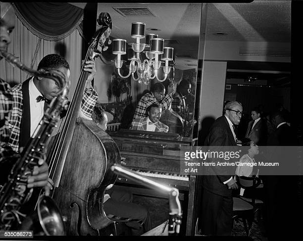 Walt Harper band performing with Nate Harper on saxophone Billy Lewis on bass and Walt Harper on piano in club with mirrored wall and Bob Dews...
