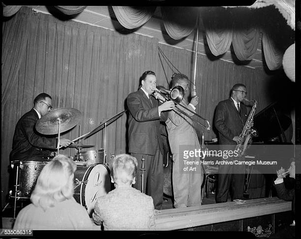 Walt Harper band with Bert Logan Jr on drums Jon Morris on trombone Walt Harper wearing light colored suit with microphone Billy Lewis on bass and...