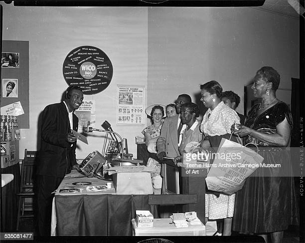 Walt Harper displaying record to group of men and women with Trower Tailor Company shopping bags in WHOD radio station booth in Syria Mosque for 1955...