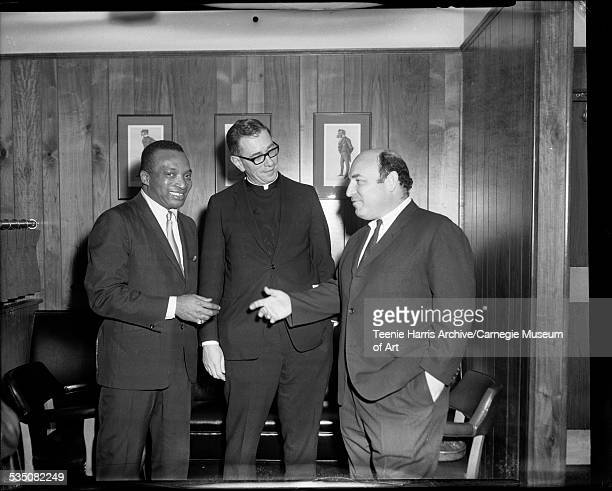 Walt Harper Father Michael Williams and George Wein posed in interior with wood paneling Pittsburgh Pennsylvania 1968