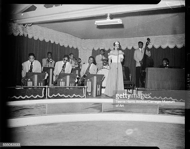 Walt Harper jazz band including Walt Harper on piano and woman wearing dress with gingham skirt singing into microphone in interior with two toned...