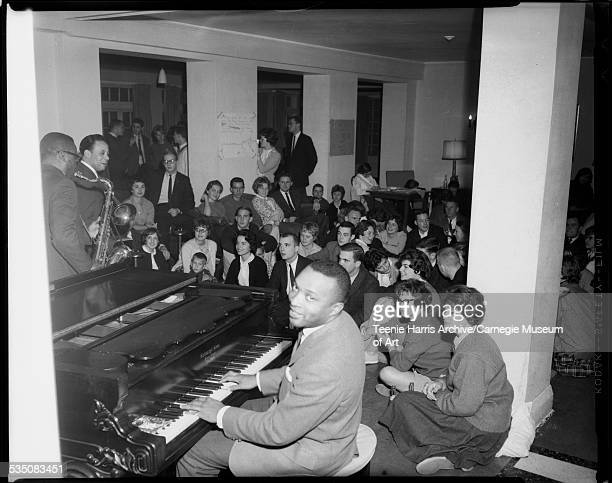 Walt Harper playing Steinway piano with Nate Harper playing saxophone and John Lewis playing trombone to audience of young men and women some seated...