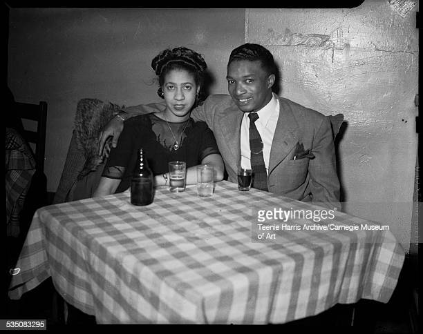 Walt Harper posed with arm around his wife Elizabeth Harper at table with plaid tablecloth in restaurant or bar Pittsburgh Pennsylvania 1946