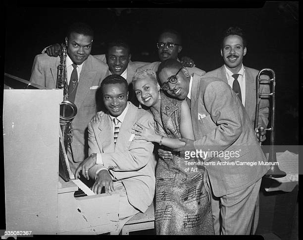 Walt Harper seated at piano with his band including Tiny Irvin and bass player Billy Lewis in front row and Nate Harper with saxophone drummer Harold...