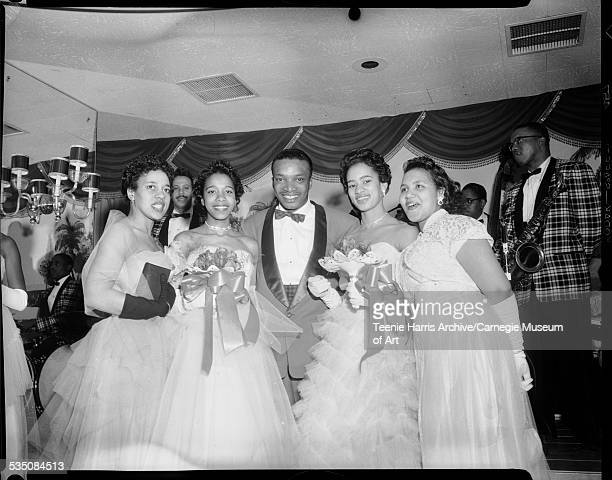Walt Harper standing in between four Alpha Kappa Alpha debutantes posed in Gateway Plaza Ballroom for Alpha Kappa Alpha 1955 Cotillion Pittsburgh...