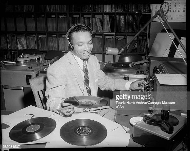 Walt Harper wearing headphones and seated at microphone with record in WHOD radio station studio with turntables reel to reel tape recorder mixer and...