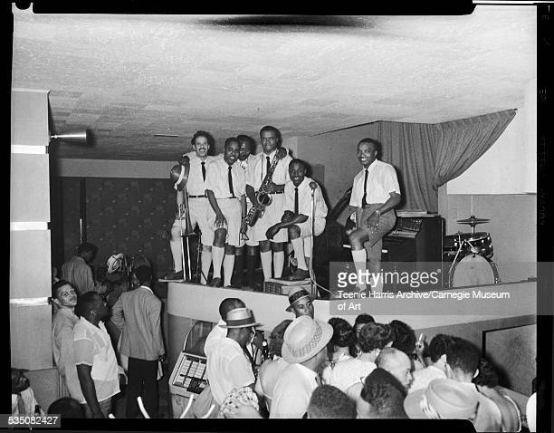 Walt Harper's band including Jon Morris on trombone Bill Lewis holding eyeglasses unknown man with arms around others Nate Harper on saxophone Howard...