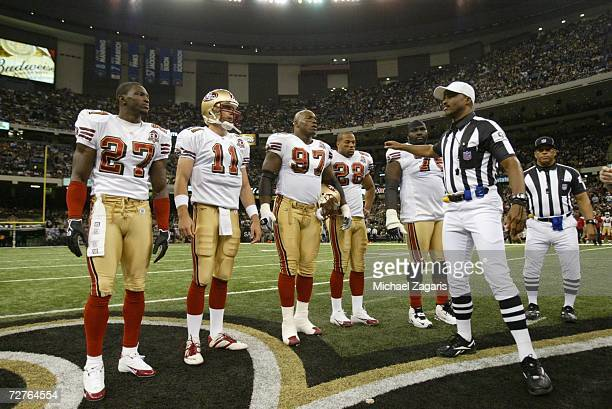 Walt Harris, Alex Smith, Bryant Young, Keith Lewis and Jonas Jennings of the San Francisco 49ers watch the coin flip by referee Mike Carey before the...