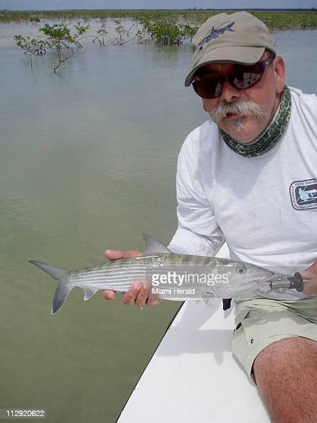 Walt Hunter holds a tagged bonefish that he caught and tagged on the flats around Grand Bahama Island June 23 2007