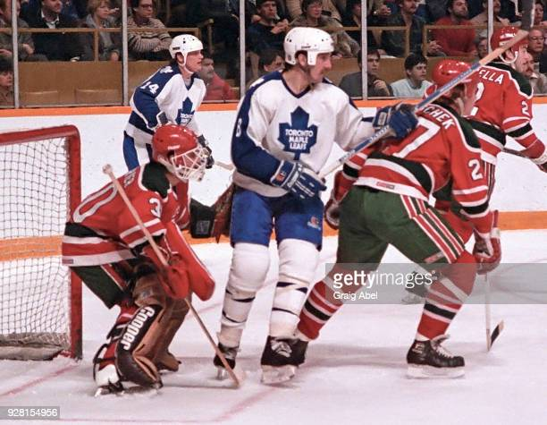 Walt Poddubny and Miroslav Frycer of the Toronto Maple Leafs skate against Alain Chevrier and Randy Velischek of the New Jersey Devils during NHL...