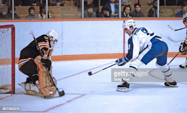 Walt Poddubny of the Toronto Maple Leafs skates against Doug Keans of the Boston Bruins during NHL game action on November 14 1985 at Maple Leaf...