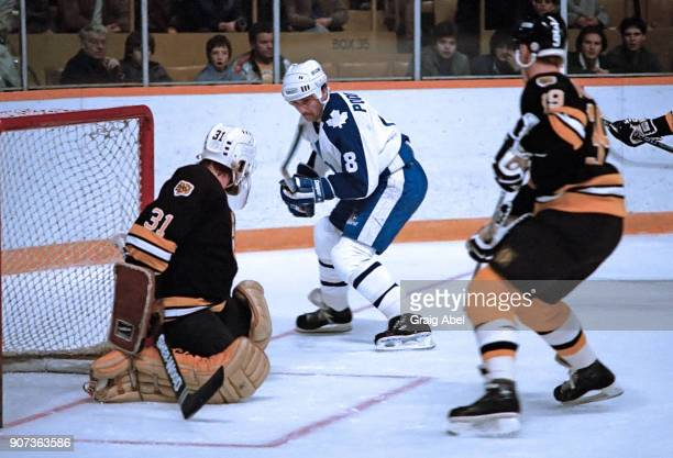Walt Poddubny of the Toronto Maple Leafs skates against Doug Keans and Greg Johnston of the Boston Bruins during NHL game action on November 14 1985...