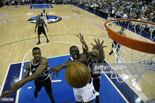 Walt Williams of the Dallas Mavericks loses the ball on the way to the basket against David Robinson and Tim Duncan of the San Antonio Spurs in Game...