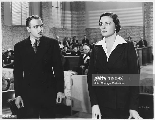 Walter Abel watches Frieda Inescort while they stand before the judge in the 1937 film Portia on Trial