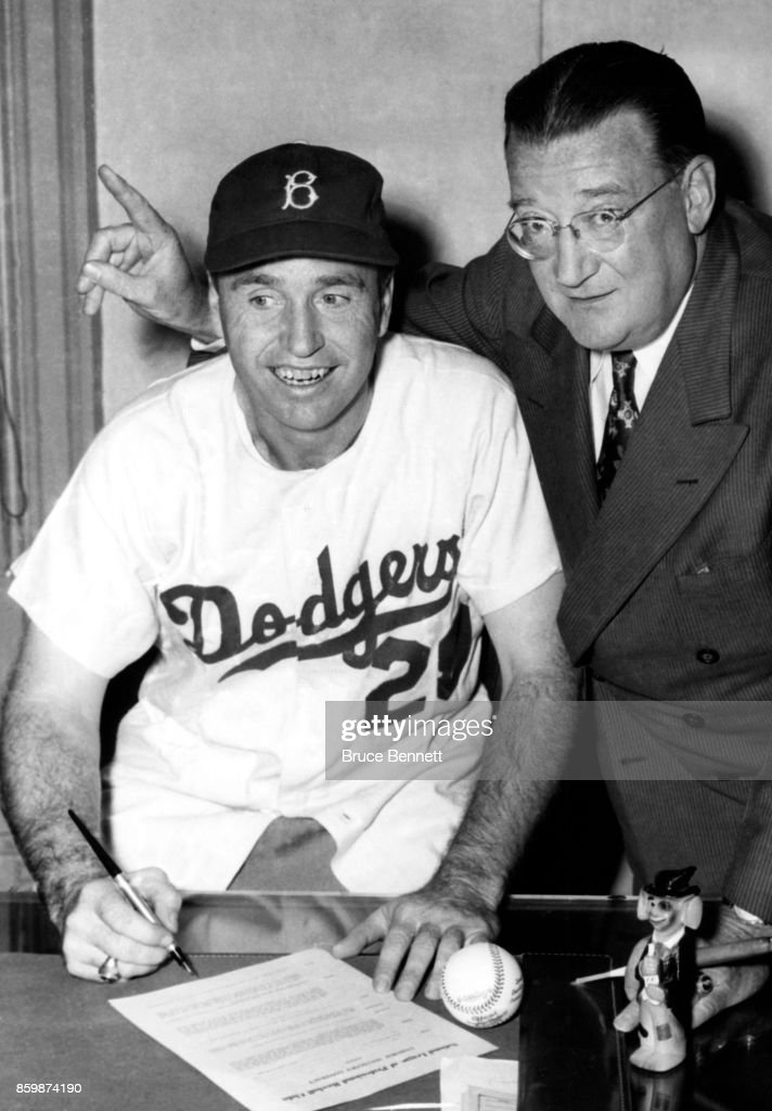 Walter Alston #24 of the Brooklyn Dodgers signs his contract to be the Dodgers manager as owner Walter O'Mally looks on circa 1954 in Brooklyn, New York.