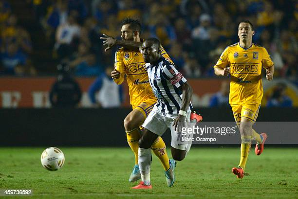 Walter Ayovi of Pachuca commits a foul on Herculez Gomez of Tigres during a quarterfinal second leg match between Tigres UANL and Pachuca as part of...