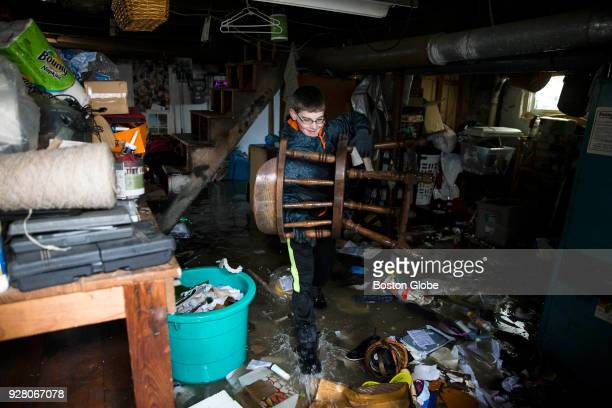 Walter Bardon removes flood damage items from the basement of his family's home in Quincy MA in the aftermath of a nor'easter storm on March 5 2018