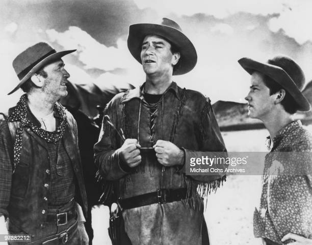 LR Walter Brennan John Wayne and Mickey Kuhn on the set of the movie 'Red River' in 1948 in the Whetstone Mountains Arizona