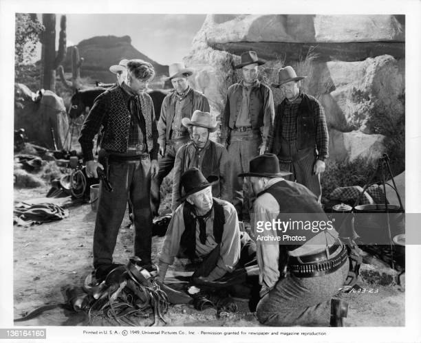 Walter Brennan, leader of the bandits, gets a farewell note from an unwilling member, delivered by his henchmen, Joe Sawyer, in a scene from the film...