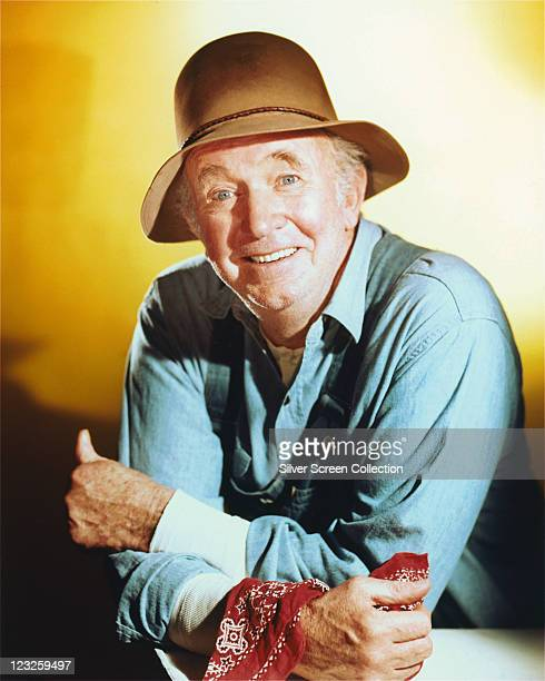 Walter Brennan US actor wearing a blue shirt and a brown hat in a studio portrait against a yellow background circa 1955
