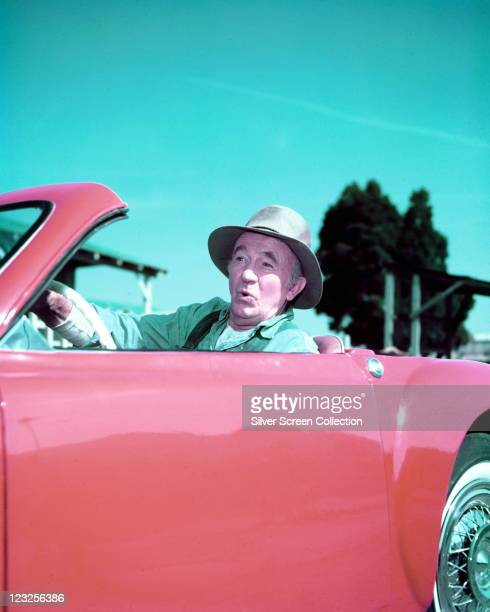 Walter Brennan US actor wearing a hat while driving a red sports car with trees and blue sky in the background circa 1965