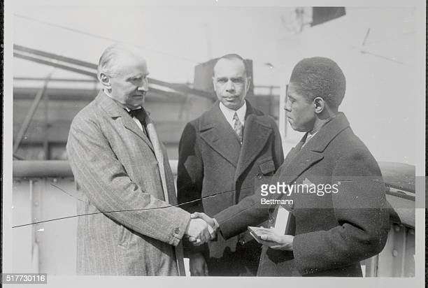 Walter Damrosh congratulates Roland Hayes negro lyric tenor after he had awarded Hayes with the Sprigarn medal Standing in the center is James W...
