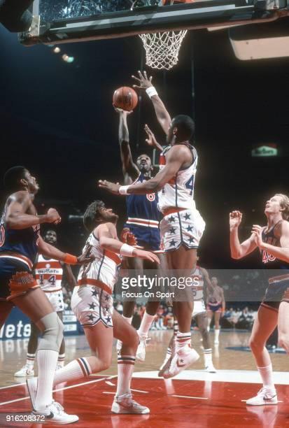 Walter Davis of the Phoenix Suns shoots over Rick Mahorn and Jeff Ruland of the Washington Bullets during an NBA basketball game circa 1982 at the...
