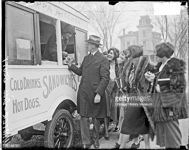 Walter Dill Scott President of Northwestern University buying a snack from a van selling food Chicago Illinois 1926