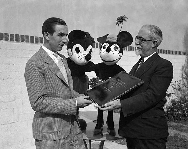 mickey and minnie mouse watching their creator receive diploma