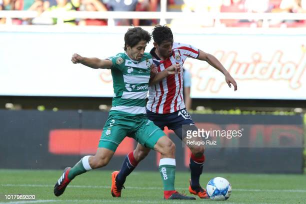 Walter Gael Sandoval of Chivas fights for the ball with Jose Abella of Santos during the fourth round match between Chivas and Santos Laguna as part...