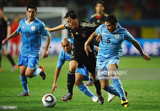 Walter Gargano of Uruguay battles for the ball with Mesut Oezil of Germany during the 2010 FIFA World Cup South Africa Third Place Playoff match...