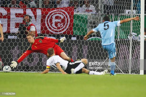 Walter Gargano of Uruguay scores his team's first goal against Philipp Lahm and goalkeeper Manuel Neuer of Germany during the international friendly...