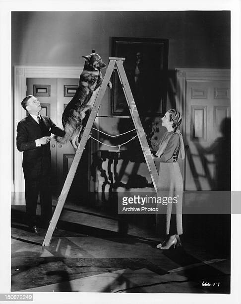 Walter Huston and Karen Morley watching dog climb up ladder in a scene from the film 'Gabriel Over The White House' 1933