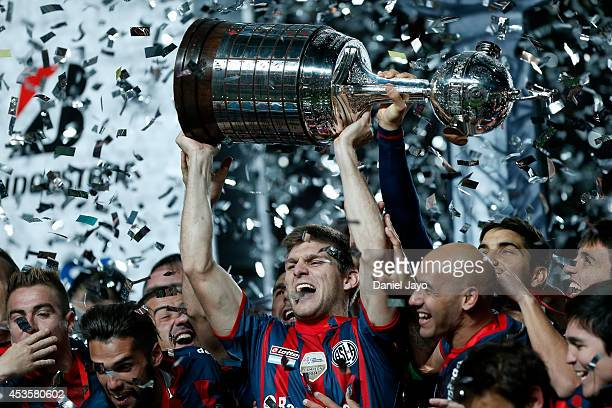 Walter Kannemann, of San Lorenzo, celebrates with the trophy at the end of the second leg final match between San Lorenzo and Nacional as part of...