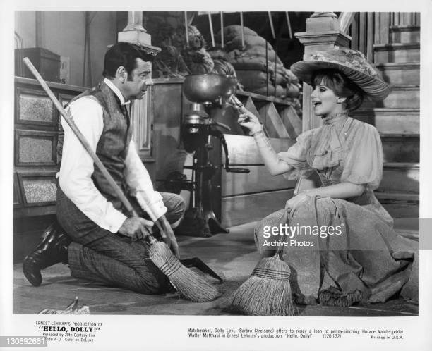 Walter Matthau and Barbra Streisand holding brooms as she tries to repay him in a scene from the film 'Hello Dolly!', 1969.