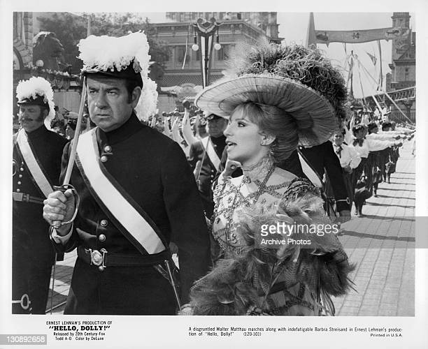 Walter Matthau marches along with Barbra Streisand in a scene from the film 'Hello Dolly' 1969