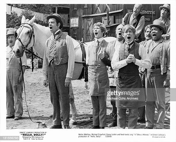 Walter Matthau, Michael Crawford, Danny Lockin and feed hands sing in a scene from the film 'Hello Dolly!', 1969.