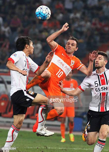 Walter Montillo of Shandong Luneng fights for the ball with Kim Chiwoo and Osmar Barba Ibanez of FC Seoul during their AFC Champions League football...