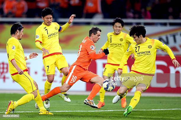 Walter Montillo of Shandong Luneng is challenged by Kashiwa Reysol players during the AFC Champions League Group E match between Shandong Luneng and...