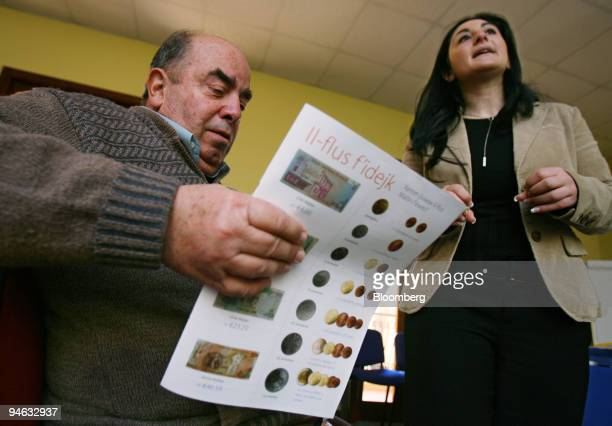 Walter Muscat of Attard Malta left looks over study materials about the euro as Carine Callus an information officer from the National Euro...