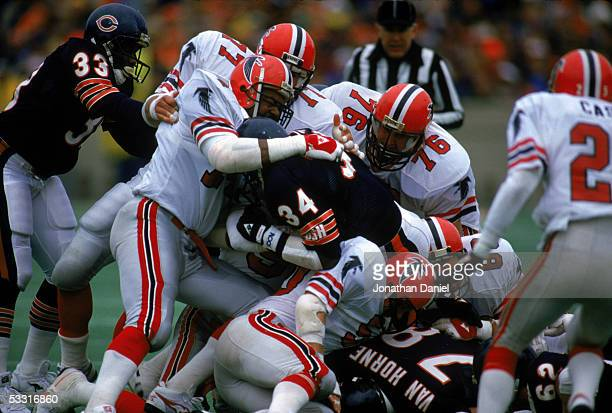 Walter Payton of the Chicago Bears is gang tackled by Atlanta Falcons defenders during the game at Soldier Field on November 24 1985 in Chicago...