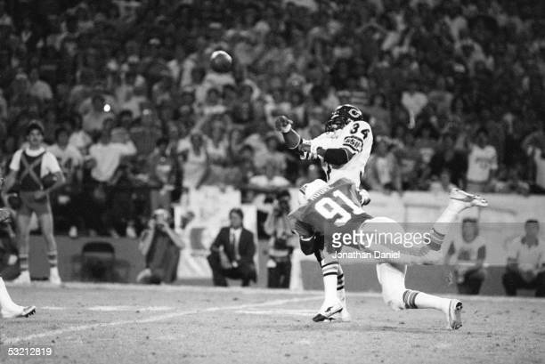 Walter Payton of the Chicago Bears throws a pass under pressure from Mack Moore of the Miami Dolphins during the game at the Orange Bowl on December...