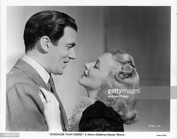 Walter Pidgeon and Virginia Bruce lean in to kiss in a scene from the film 'Stronger Than Desire' 1939