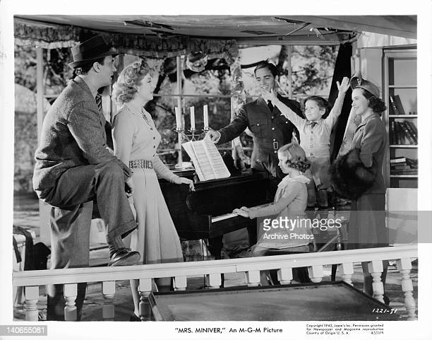 Walter Pidgeon Greer Garson Richard Ney and Teresa Wright gathered around the piano to hear a young girl play in a scene from the film 'Mrs Miniver'...