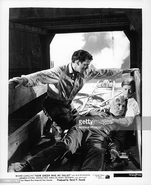 Walter Pidgeon hanging over child and a dazed Donald Crisp in a scene from the film 'How Green Was My Valley', 1941.