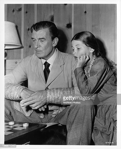 Walter Pidgeon plays checker as he wears straw cuffs around his wrists Donna Corcoran stands and watches in amazement in a scene from the film...